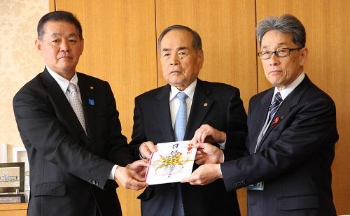 目録を手渡す黒川副社長(右:梶市長、左:大前議長)