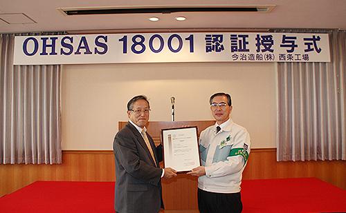 OHSAS18001認証証書を持ち、記念写真に収まる日本海事協会 冨士原副会長(左)と当社日高工場長