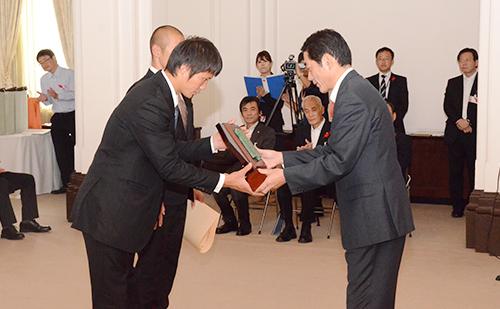 中村時広愛媛県知事より表彰状を授与される井出主将と別府選手。
